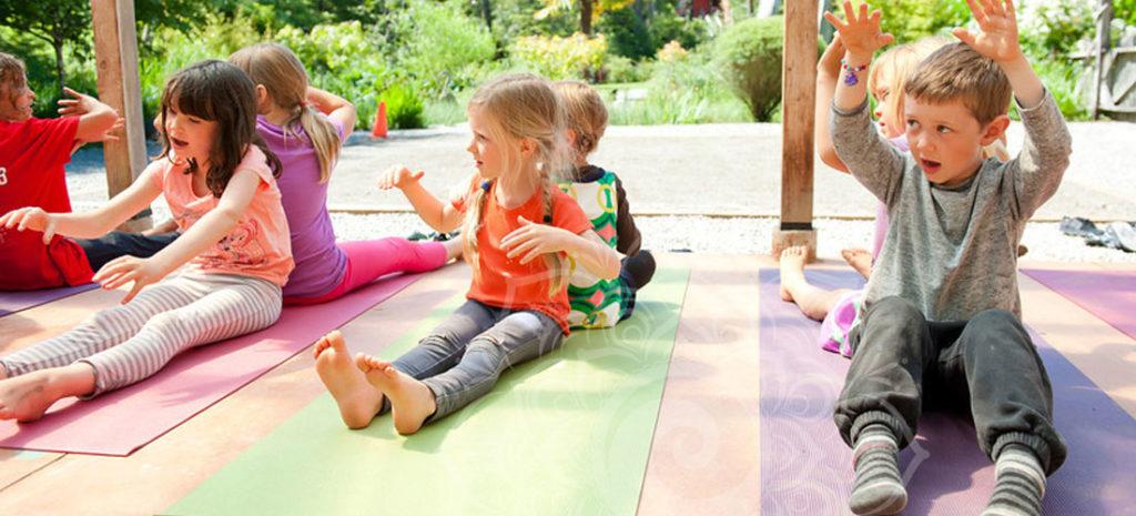 Kids doing yoga on colorful yoga mats